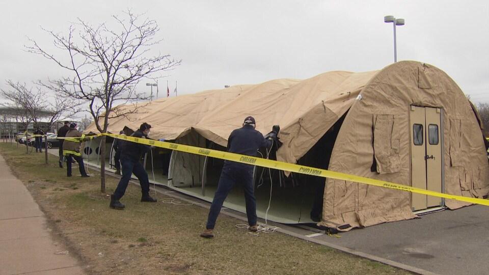 Environ 5 personnes tirent la toile d'une grande tente rigide brune. Autour de la tente, un ruban jaune d'urgence a été installé.
