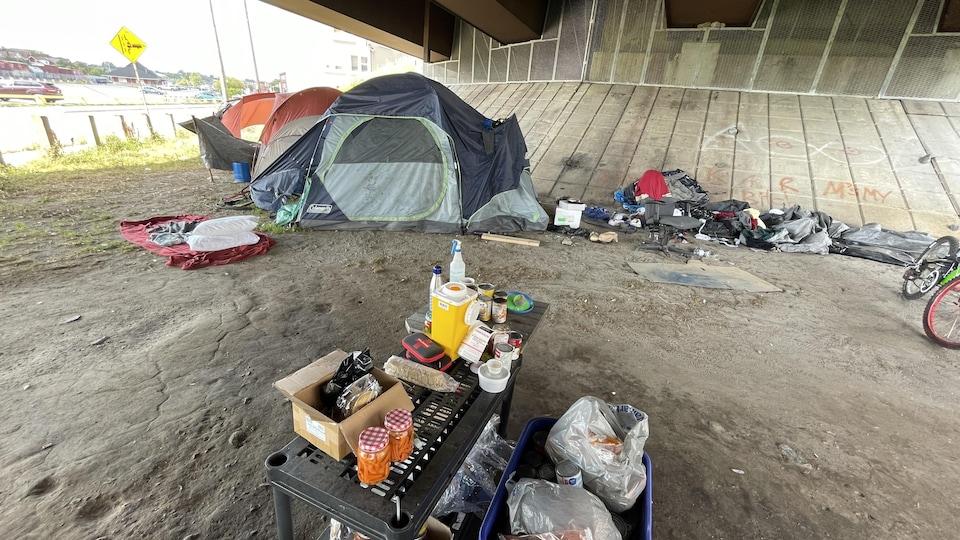 Des tentes et des affaires de sans-abri sous un pont.
