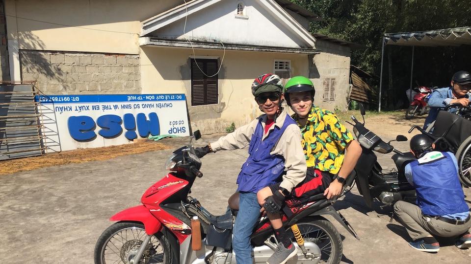 Téo assis à l'arrière d'une moto. Le conducteur de la moto et lui portent des casques de protection.