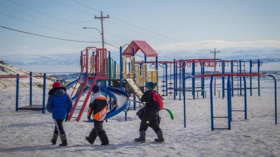Des enfants vêtus chaudement traversent un terrain de jeu devant un paysage montagneux.