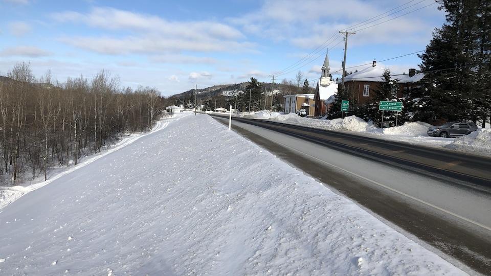 Un terrain enneigé en pente borde la route 155.