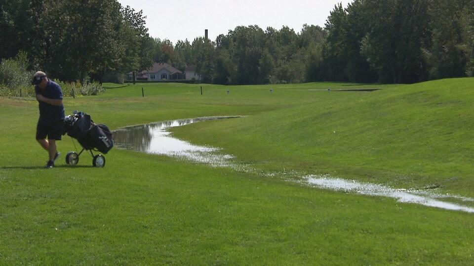 Un golfeur sur le terrain avec de l'eau.