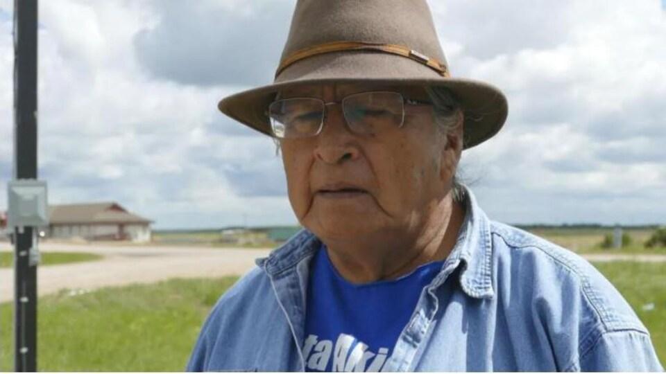 Un homme de la communauté autochtone Birdtail Sioux devant un vaste espace en milieu rural.