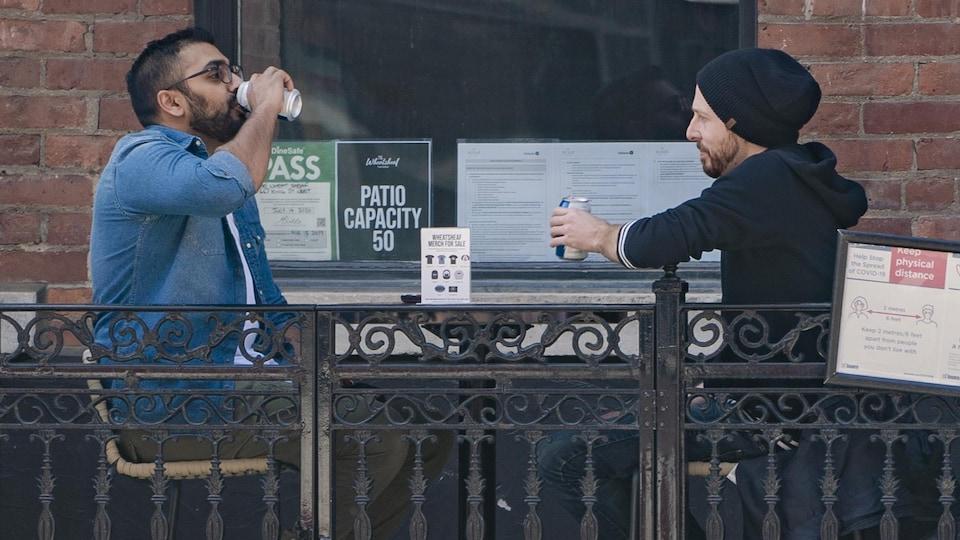Deux hommes attablés à une terrasse boivent une bière.