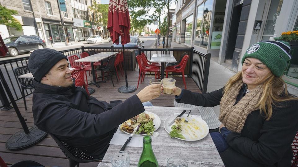 Deux personnes trinquent avec leur verre de café sur la terrasse d'un restaurant.