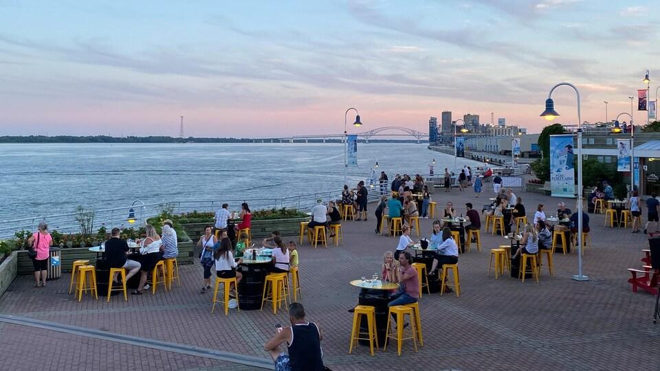 Gens assis à des tables près du fleuve.