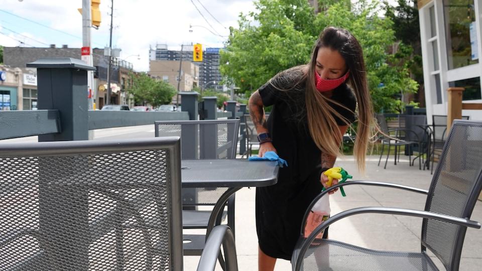 Une femme portant un masque nettoie une table sur une terrasse de restaurant.