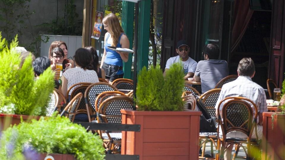 Des gens se retrouvent sur une terrasse extérieure, le temps d'une bière.