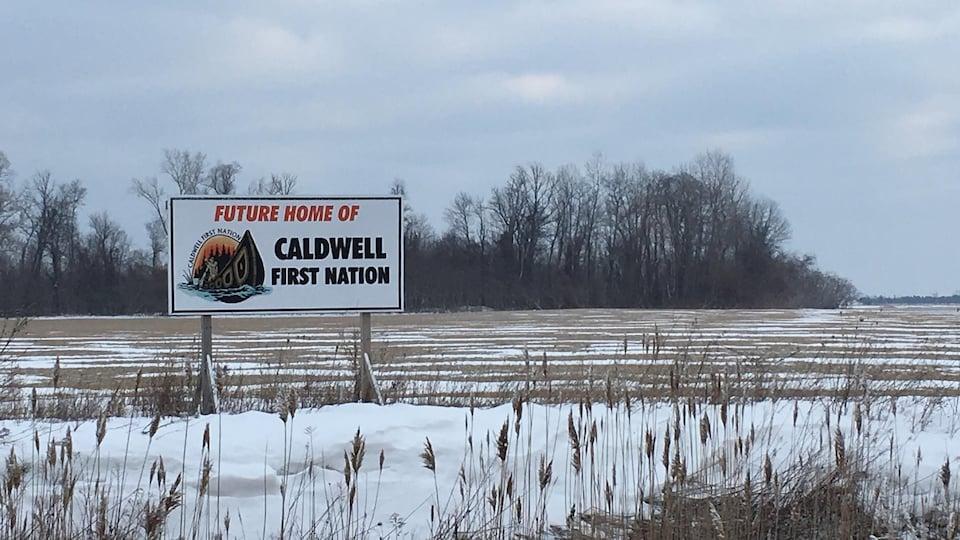 """Vue d'un champ en hiver. De la neige est au sol. Un panneau qui dit """"Futur Home of Caldwell First Nation"""" est à l'avant-plan."""