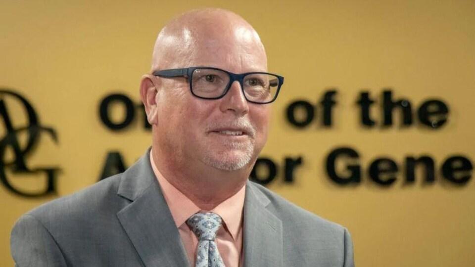 Un homme avec des lunettes vêtu d'un complet gris devant un mur jaune.