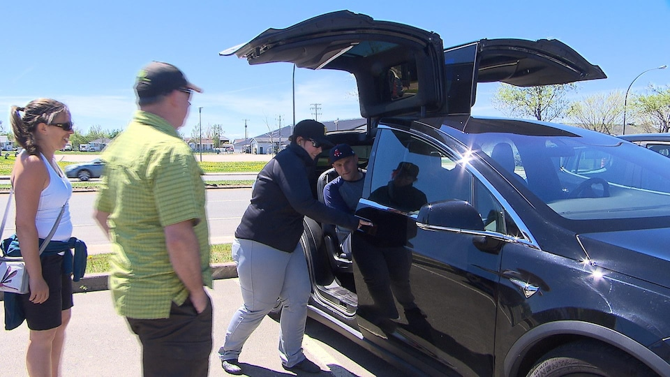 Un homme s'installe dans une Tesla par des portes s'ouvrant de bas en haut.