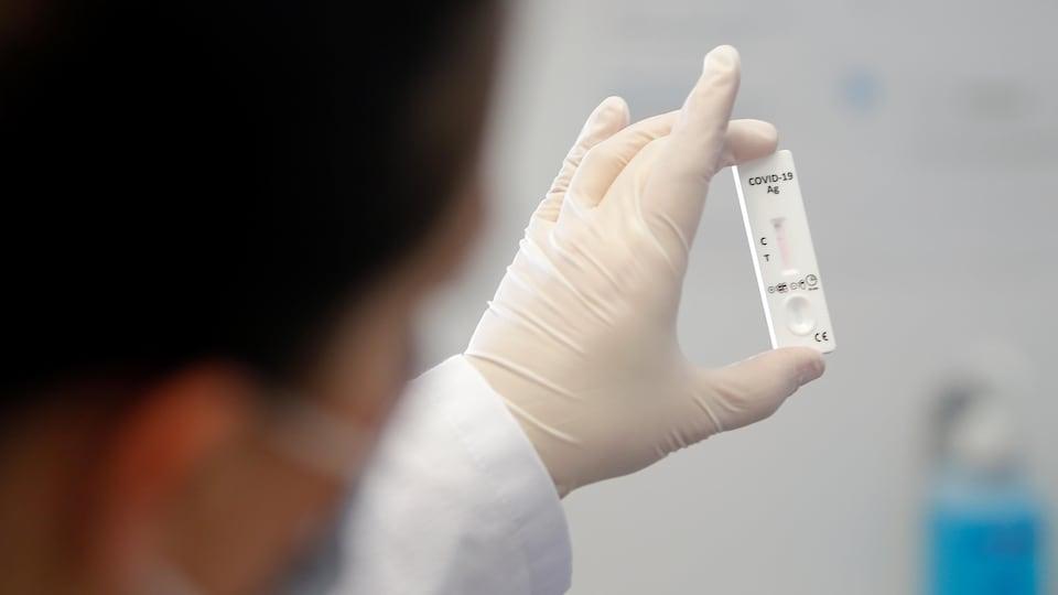 Un travailleur de laboratoire examine un test de COVID-19.