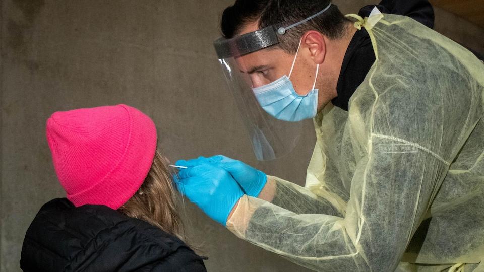 Un travailleur de la santé prélève un échantillon sur une femme, de dos.