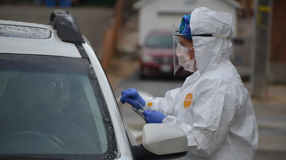 Une personne portant des équipements de protection effectue un test de dépistage de la COVID-19 pour un homme dans une voiture.