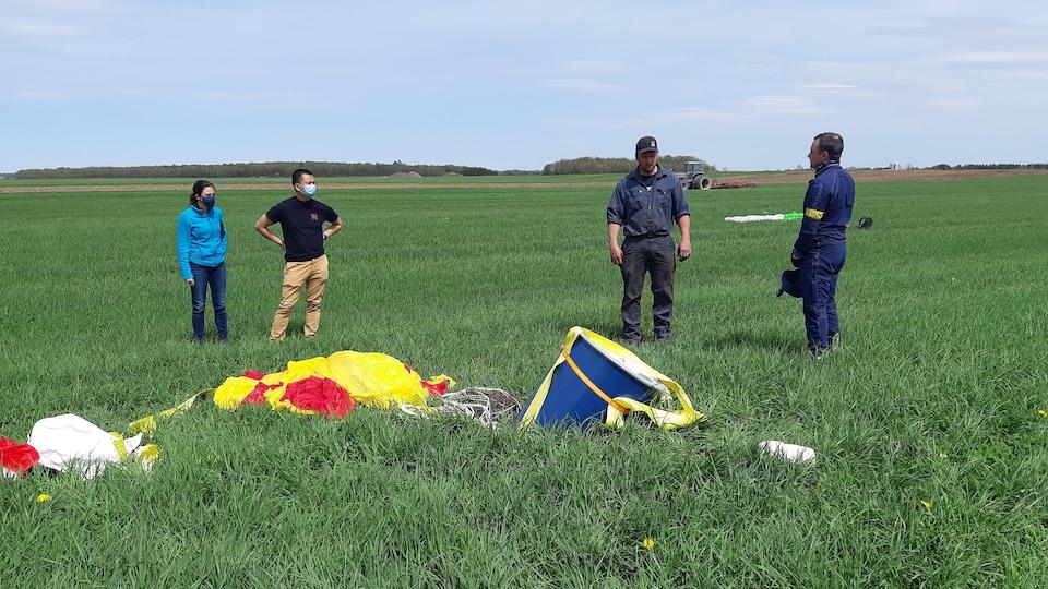 Quatre personnes regardent un baril attaché à un parachute qui s'est écrasé dans un champ.