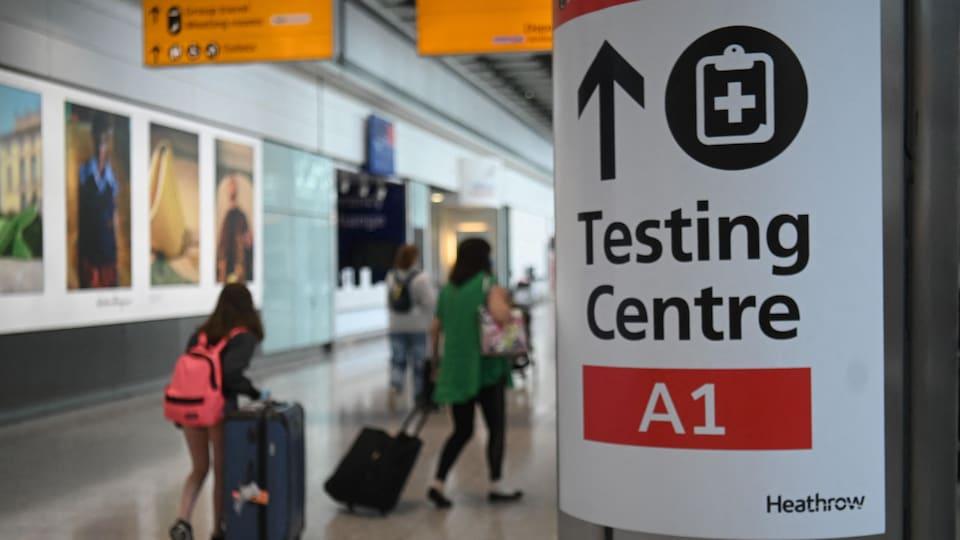 Des passagers marchent avec leurs valises devant une affiche pour le centre de prélèvement.