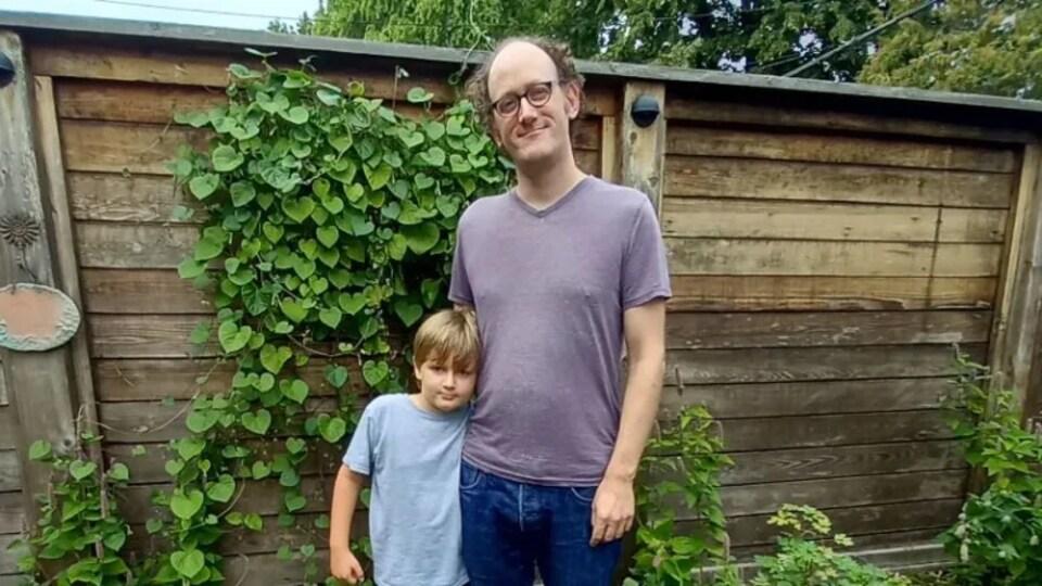 Un homme et un garçon se tiennent debout et regardent la caméra.