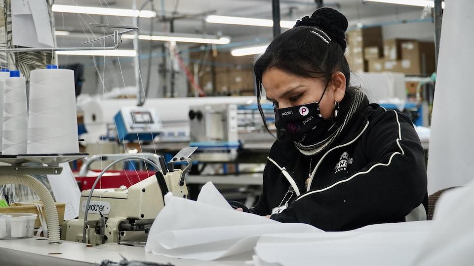 Une couturière avec un masque qui coud une blouse de protection dans l'usine.