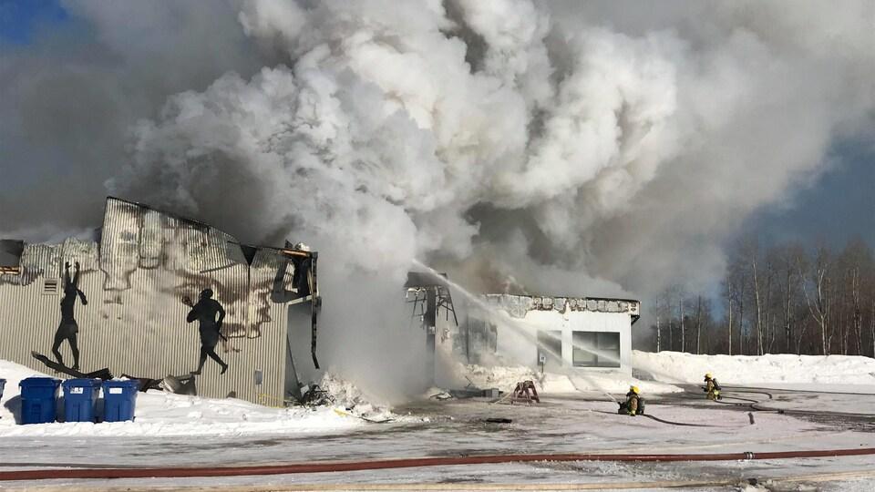 Des pompiers agenouillés dans la neige tente d'éteindre l'incendie.
