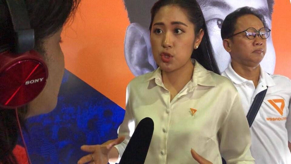 Une jeune femme répond à des questions d'une journaliste.