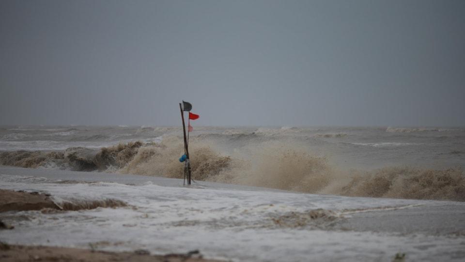 Un drapeau rouge est planté dans le sable. Derrière, de grosses vagues agitent l'océan.
