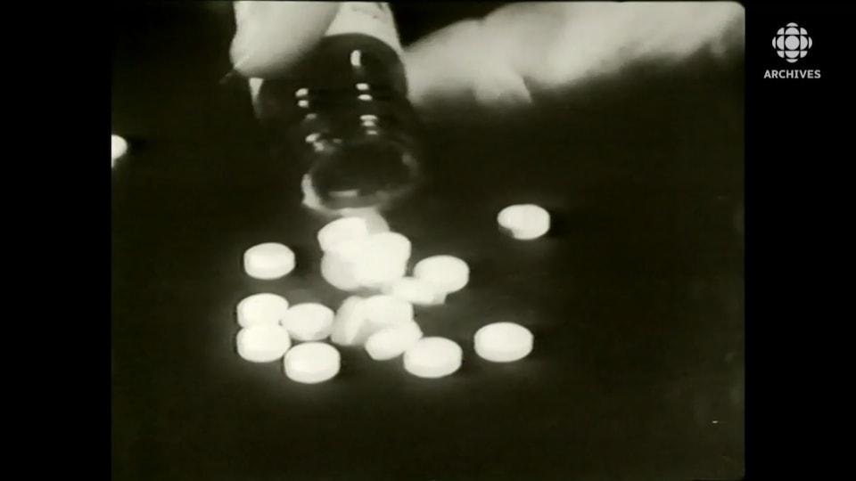 Plan rapproché d'une bouteille déversant des pilules blanches connues sous le nom de thalidomide.