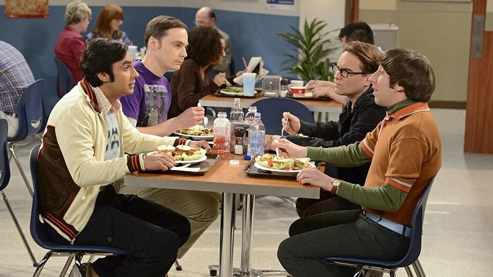 Les quatre personnages principaux de la série « The Big Bang Theory » sont assis autour d'une table, mangent et discutent. D'autres personnes sont assises à d'autres tables.