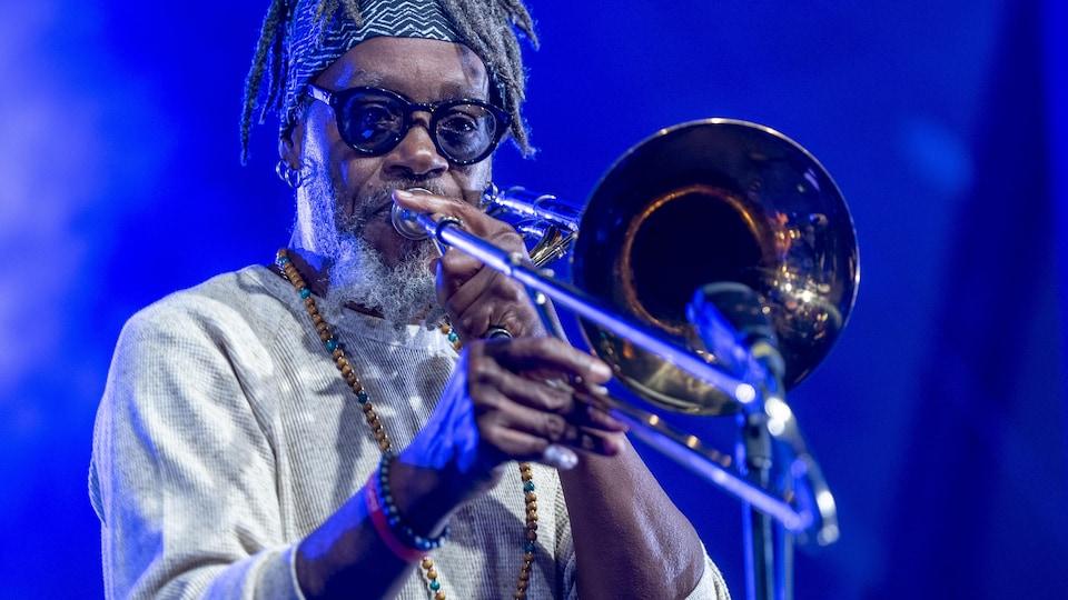 Un musicien joue de la trompette sur scène.