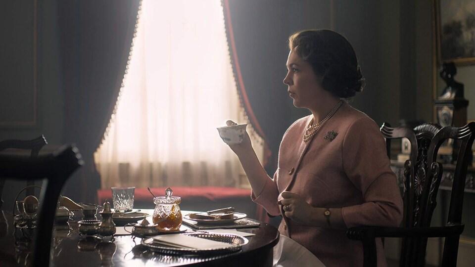 L'actrice, vêtue de rose, tient une tasse de thé dans une main.