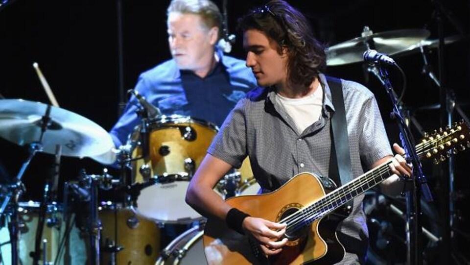 Le musicien au premier plan joue de la guitare, celui derrière est à la batterie.