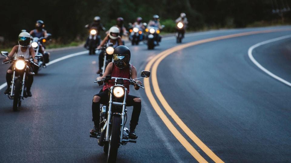 Des femmes conduisent en motocyclette une derrière l'autre sur l'autoroute.