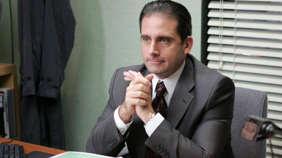 Un homme en complet-cravate assis à son bureau, le regard vers l'avant.