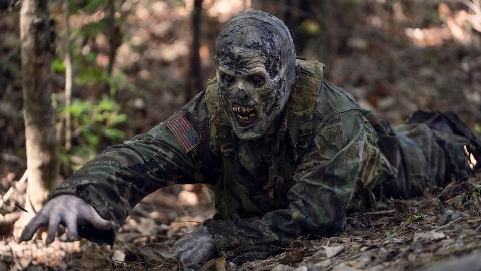 Un zombie en tenue de soldat américain rampe sur le sol dans la forêt.