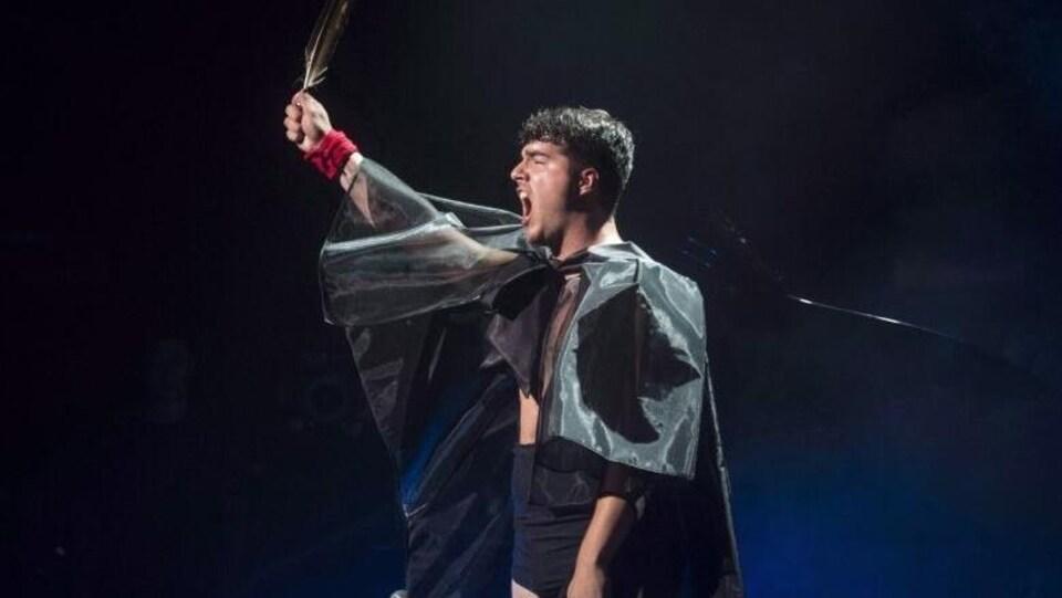 Le chanteur est installé devant un micro, le bras levé, brandissant une plume.