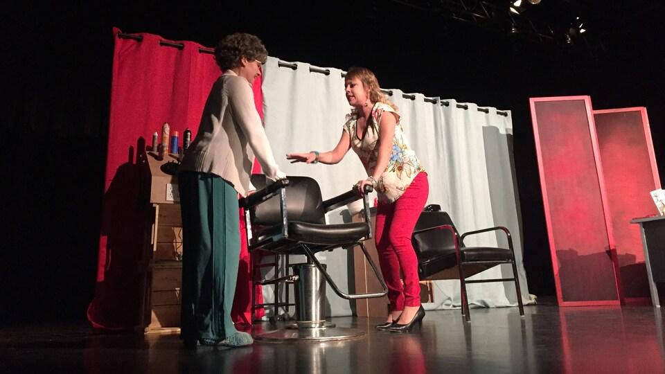 Deux comédiennes, une incarnant une dame âgée et une autre une coiffeuse, sont sur scène et tiennent une chaise dans un décor de salon de coiffure.