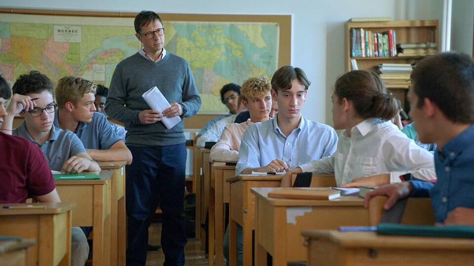 Un professeur est debout dans une salle de classe, alors que plusieurs jeunes se tournent vers l'un d'eux.