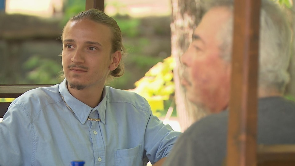 Un jeune homme assis face à un homme plus âgé