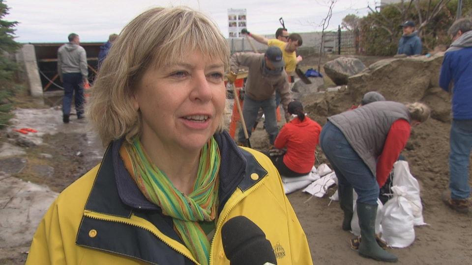 Theresa Kavanagh en entrevue alors que des gens remplissent des sacs de sable derrière elle.