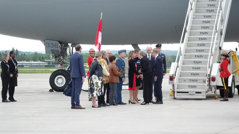 Une femme serre la main à plusieurs personnes. Elle vient de descendre d'un avion.