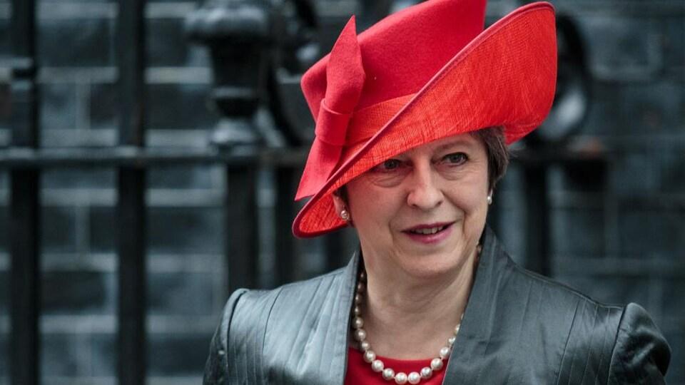 Plan rapproché de Mme May, qui porte un grand chapeau asymétrique.