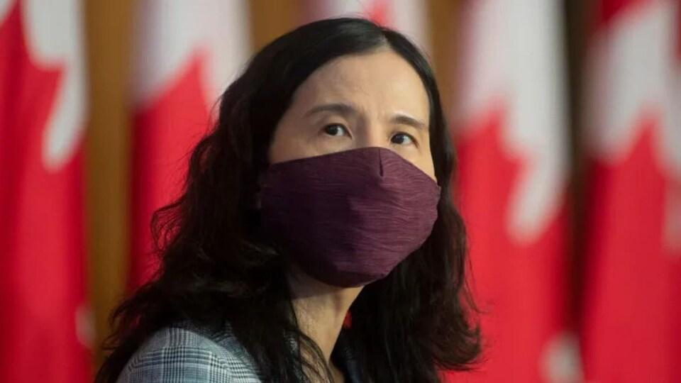 Theresa Tam, masque au visage, devant des drapeaux canadiens.