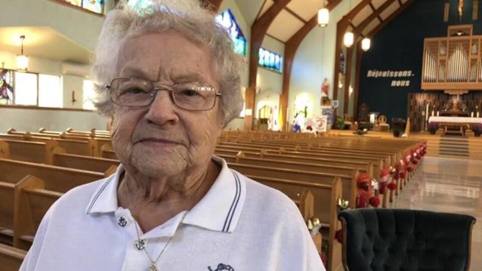 Portrait d'une vieille dame entre des bancs d'église.