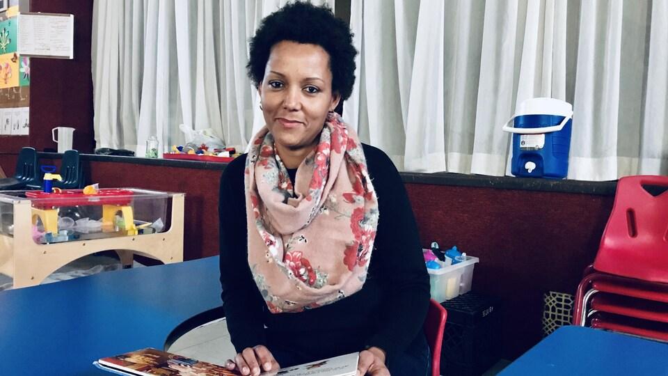 Une femme assise avec un livre.