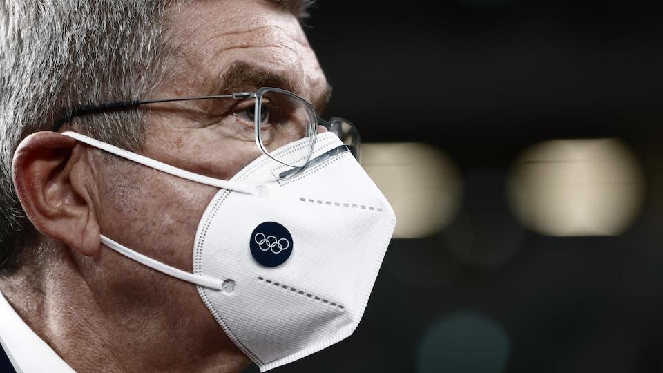 Gros plan du président du Comité international olympique avec un masque portant le logo olympique.