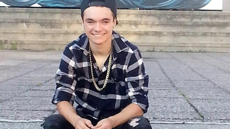 Le jeune homme assis à l'extérieur, souriant