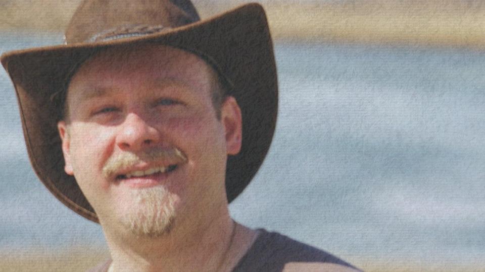 Un homme avec un chapeau de cowboy sourit.