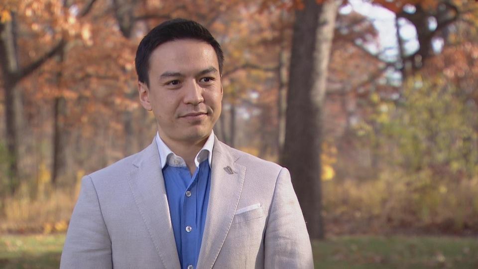 Un homme debout à l'extérieur dans un parc, un jour d'automne.