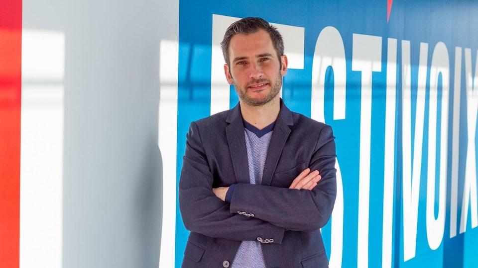 Thomas Grégoire devant une affiche du festivoix.