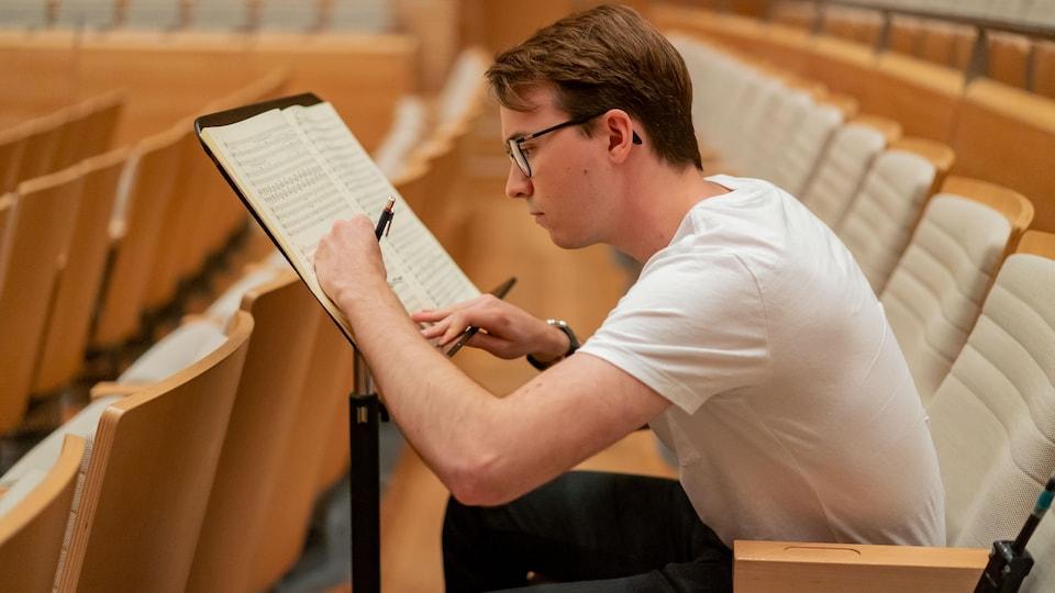 Le jeune homme écrit des notes au stylo sur des partitions posées sur un lutrin, assis dans l'un des sièges d'une salle de spectacle.