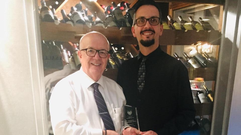Le fondateur du restaurant Memories Dining & Bar Thomas Siarkos (à gauche) tient une plaque avec Nikita Selimos (à droite), désormais co-propriétaire.